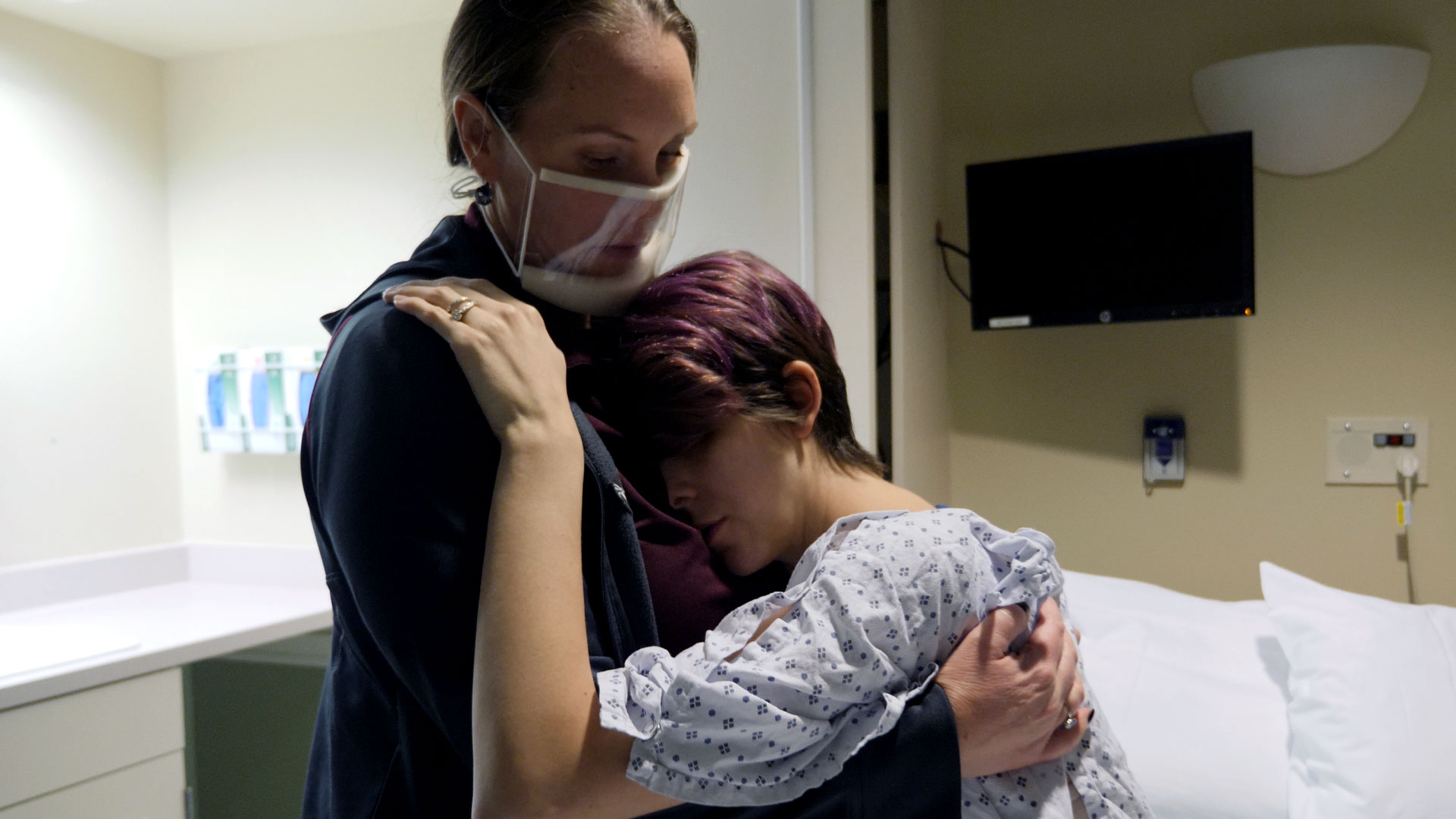 Doula holds pregnant woman in hospital room.